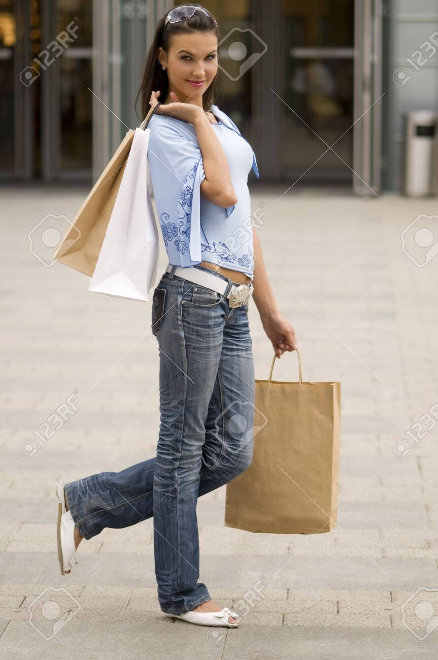cute brunette standing in front of a commercial center keeping some bags in hands Stock Photo - 3258003