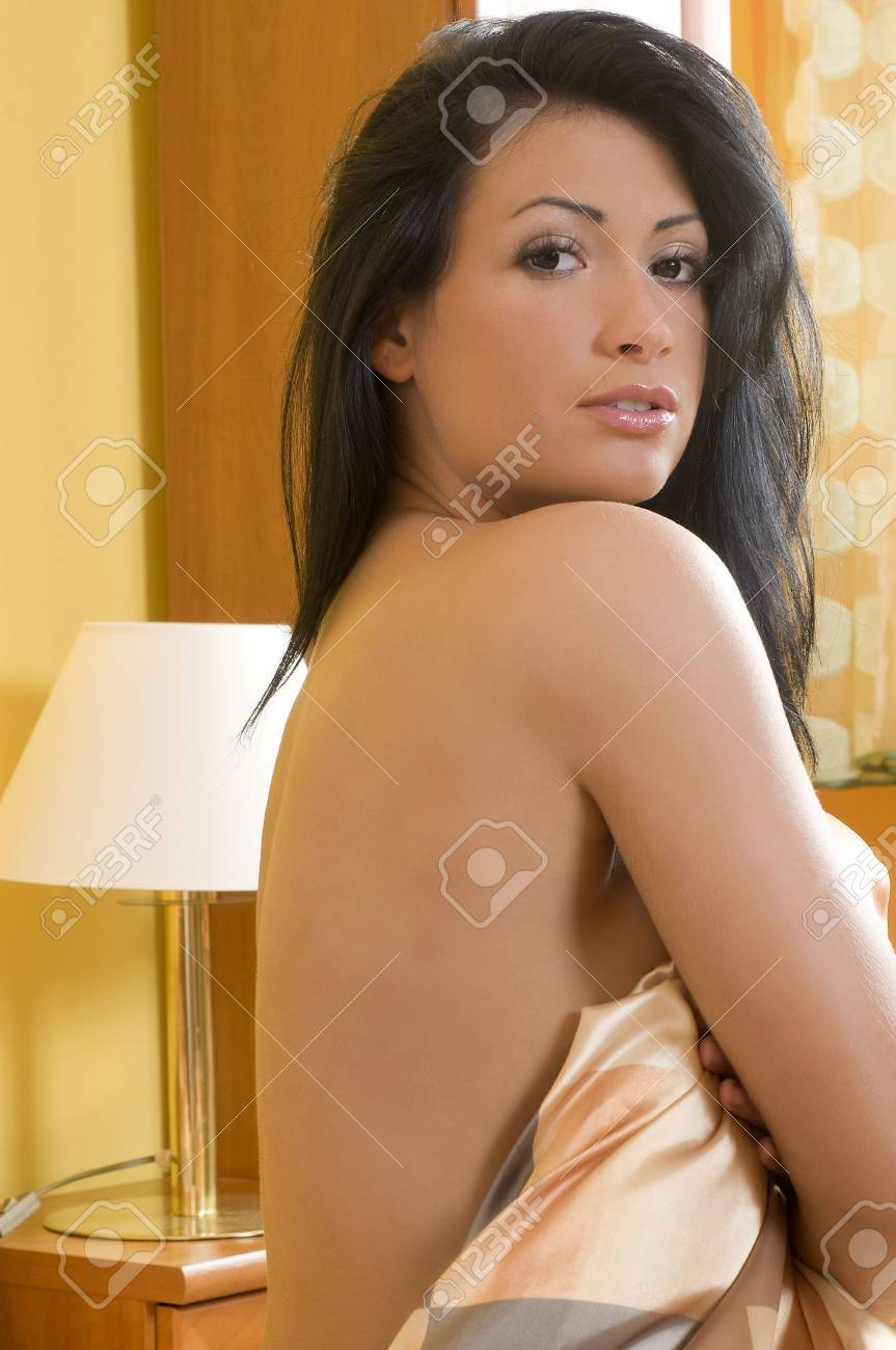 sexy brunette in bed covering her body with bedsheet and showing her shoulder Stock Photo - 3307902
