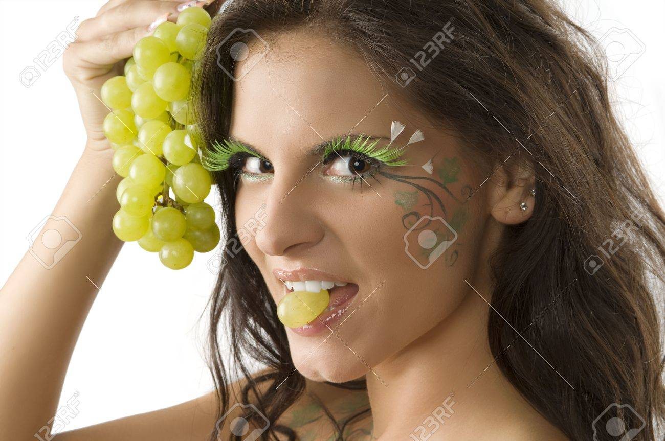 Stock Photo   pretty girl with a grape between the teeth and her face  painted with green leaf. Pretty Girl With A Grape Between The Teeth And Her Face Painted
