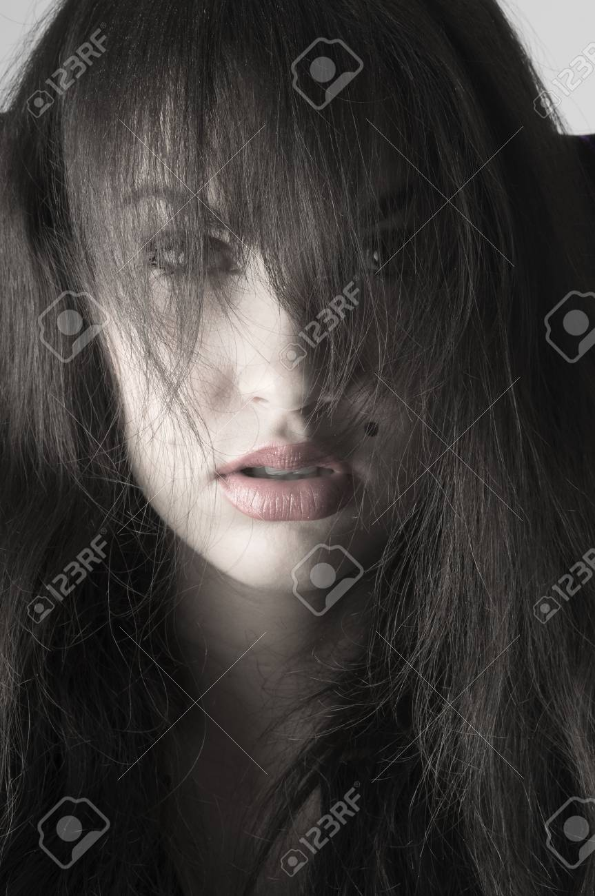 cute brunette with  long hair on her face in a desaturated portrait Stock Photo - 3664803