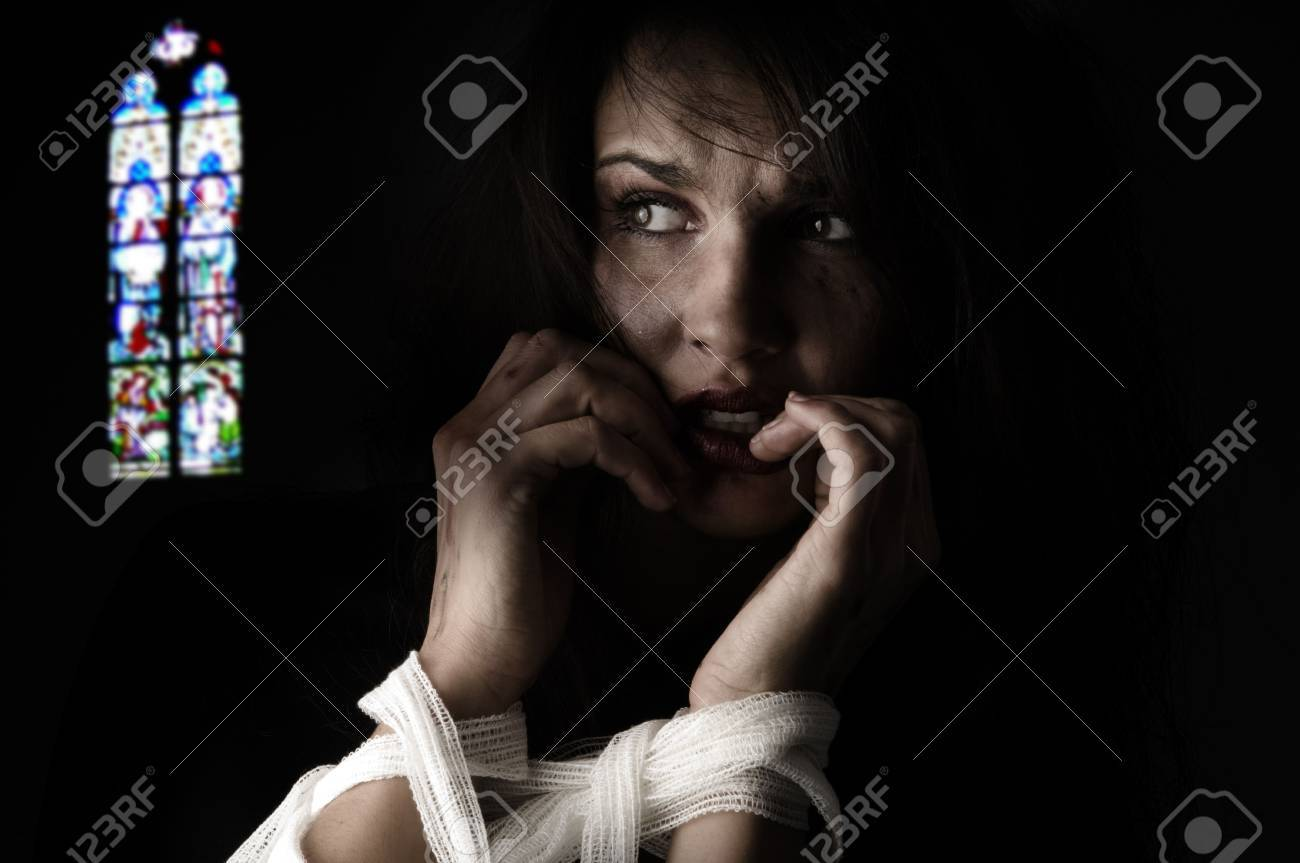 woman in fear with patch around her arms an a church windows on back Stock Photo - 3689588