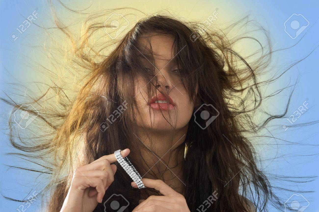 cute brunette playing with silver jewel and windly hair Stock Photo - 4006879