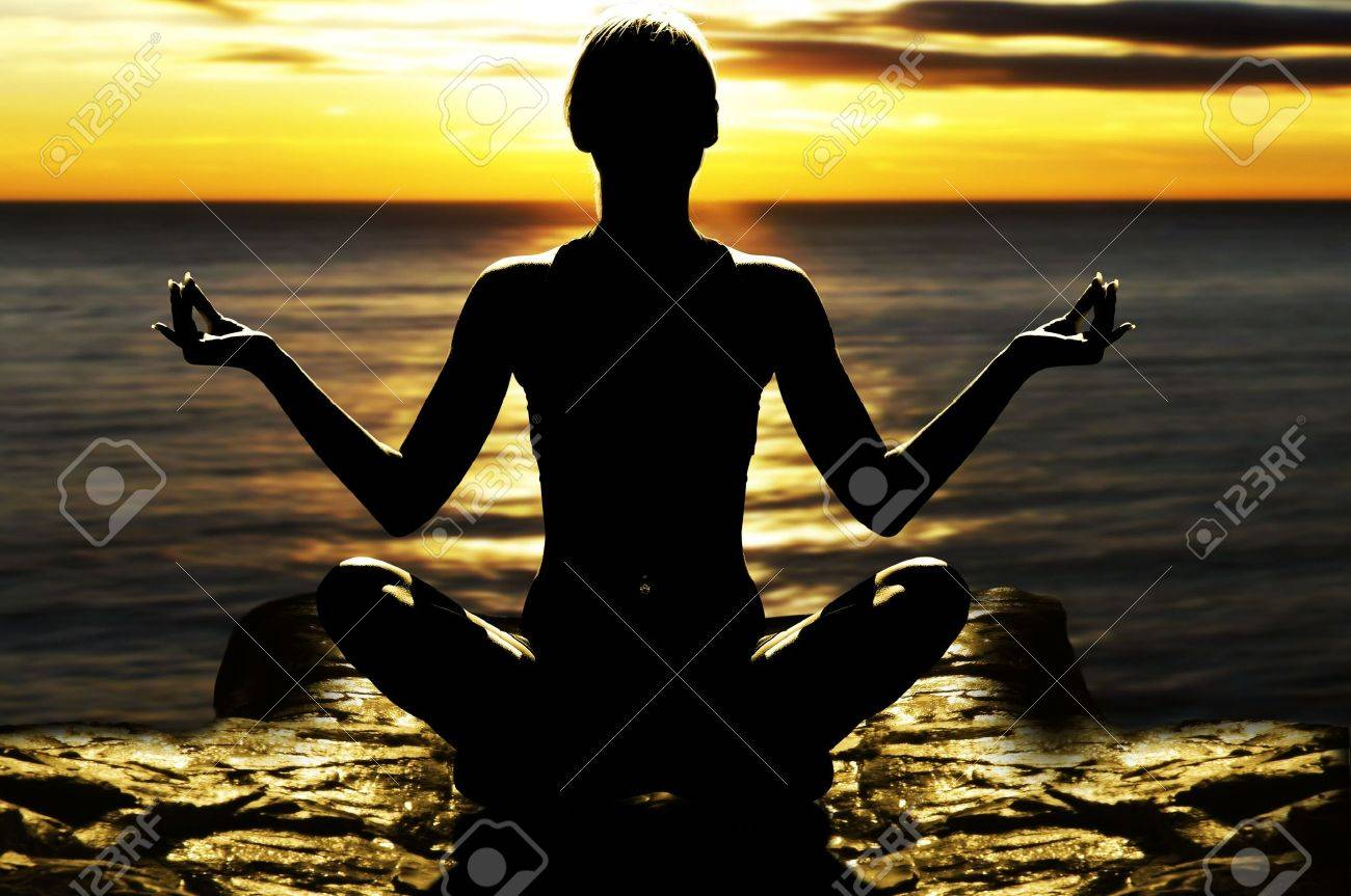 silhouette of woman on rock in the sunset sea in a classic yoga pose Stock Photo - 4652966