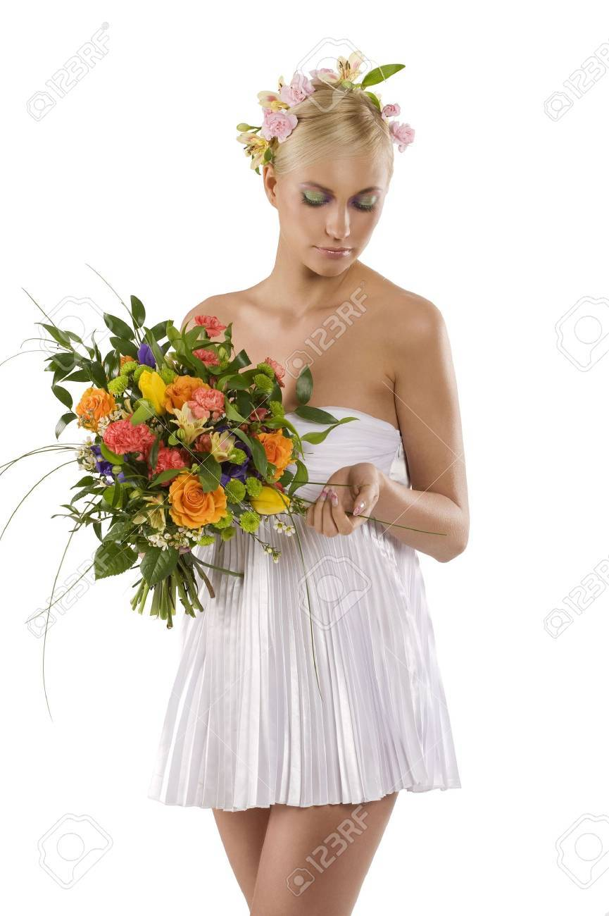 young and beautiful woman in short white dress with flower in hair and keeping a color bouquet Stock Photo - 6540386