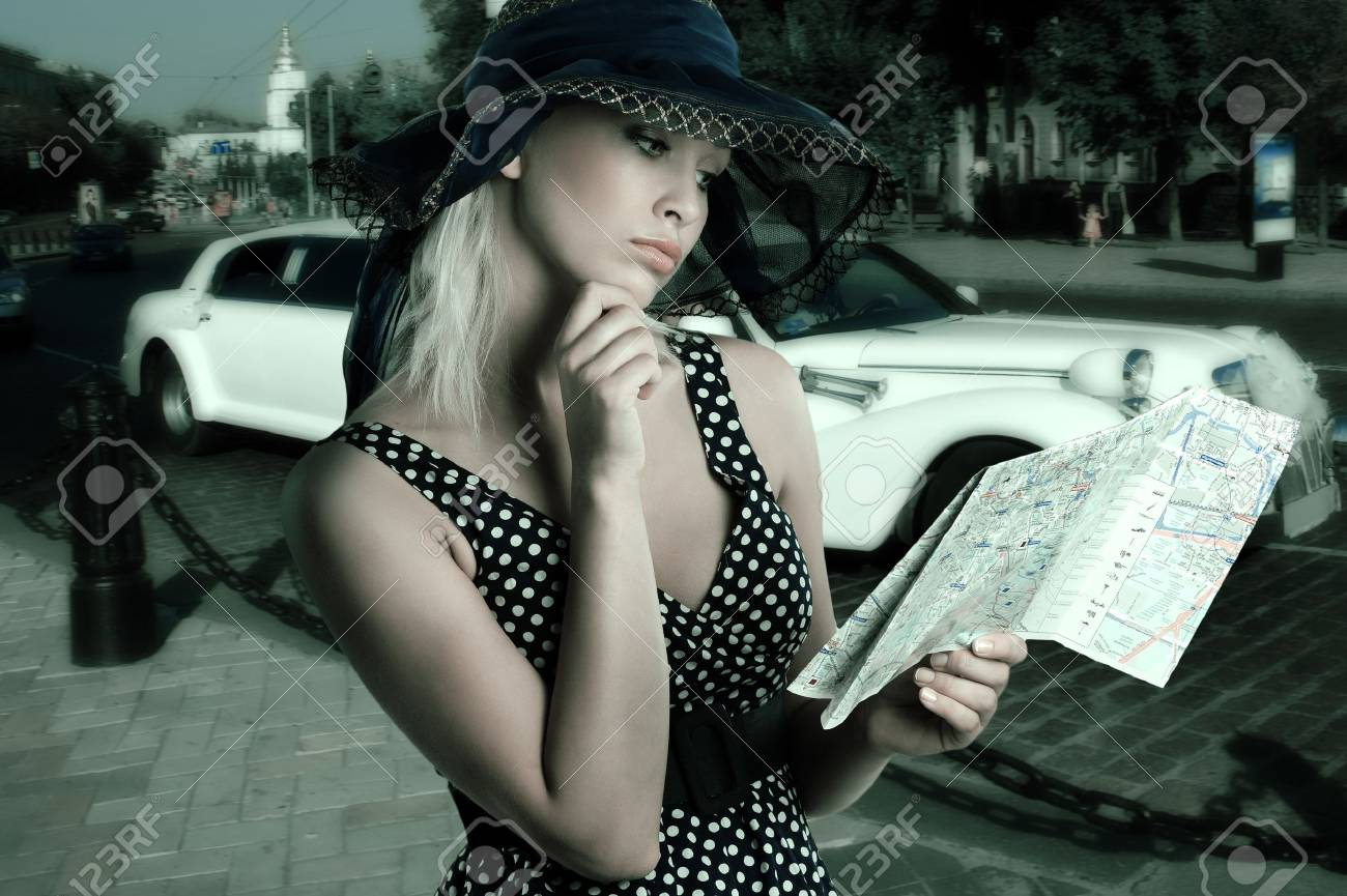 elegant woman in blue polka dot dress and hat looking at a tourist map Stock Photo - 7717939