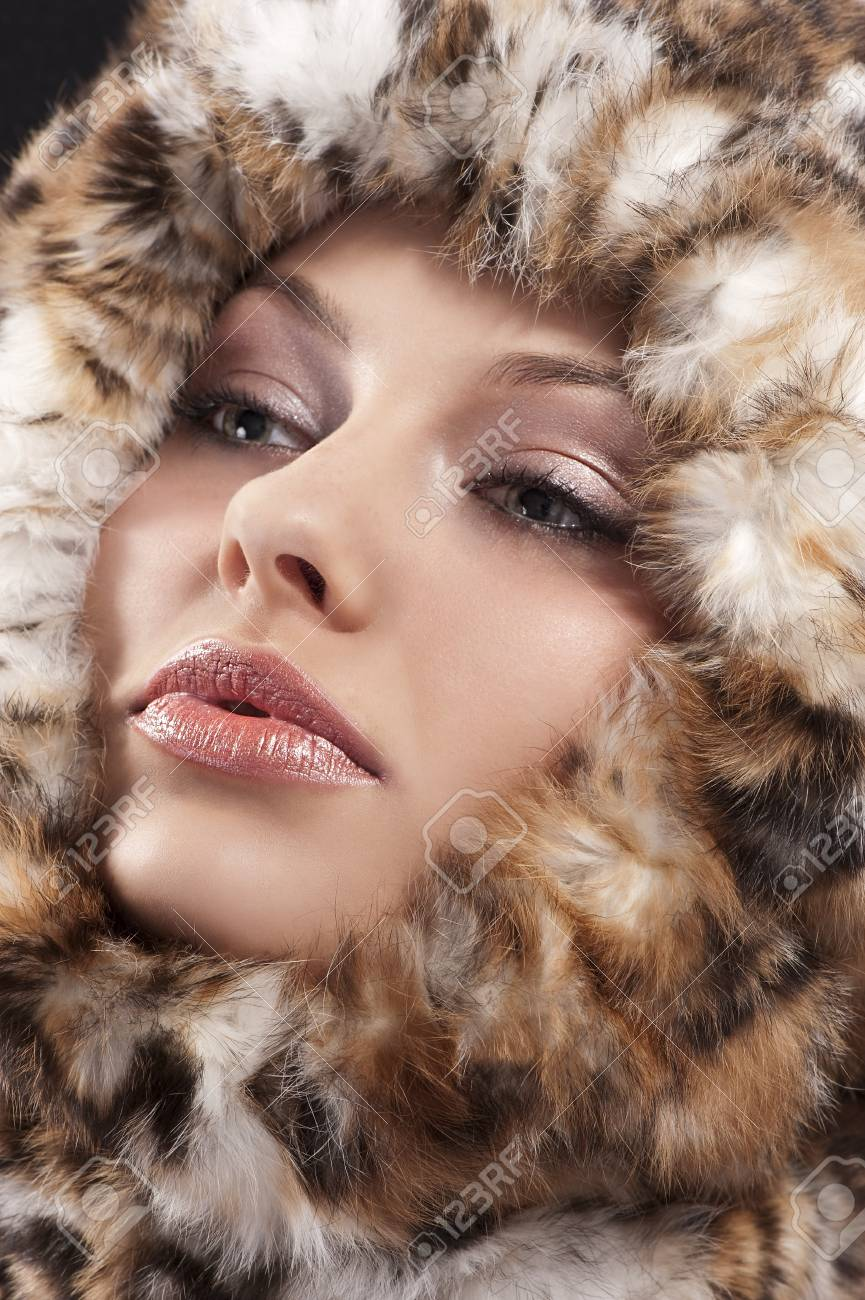 fashion close up portrait of a young pretty girl with a fur all around her face looking on one side Stock Photo - 10550459