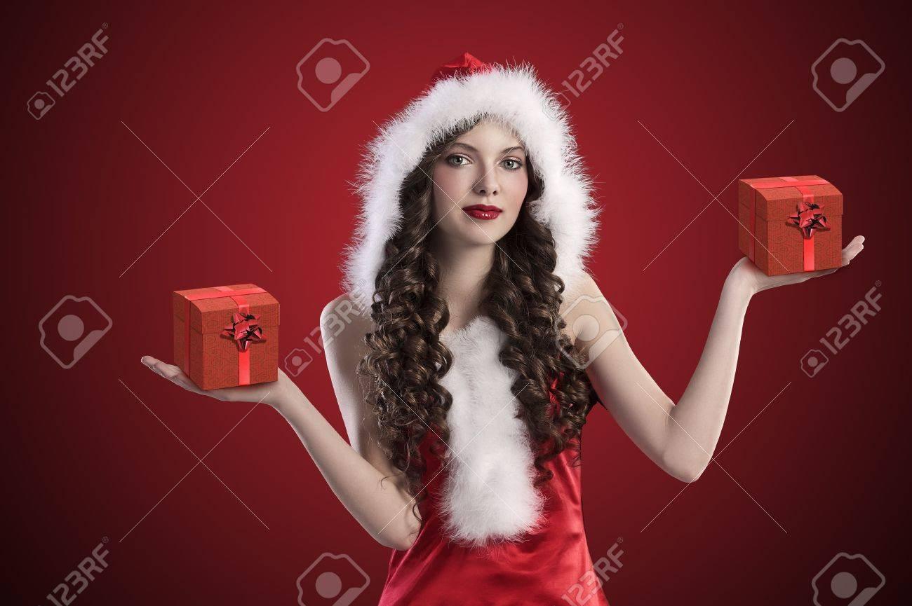 dulce chica morena con el pelo natural de largo rizado y llevaba un traje de Santa Claus rojo con capucha de piel y abriendo los brazos Foto de archivo - 11303195