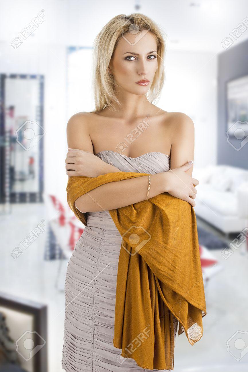 Foto de archivo , elegante mujer muy joven con una bufanda larga y un  vestido ligero, ella mira a la lente y los brazos cruzados son