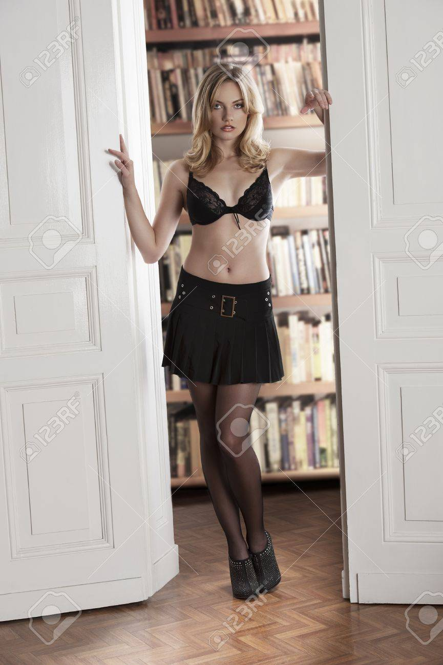 young sexy blond girl wearing a black bra and a  black mini skirt taking pose near old fashioned white doors Stock Photo - 12362071