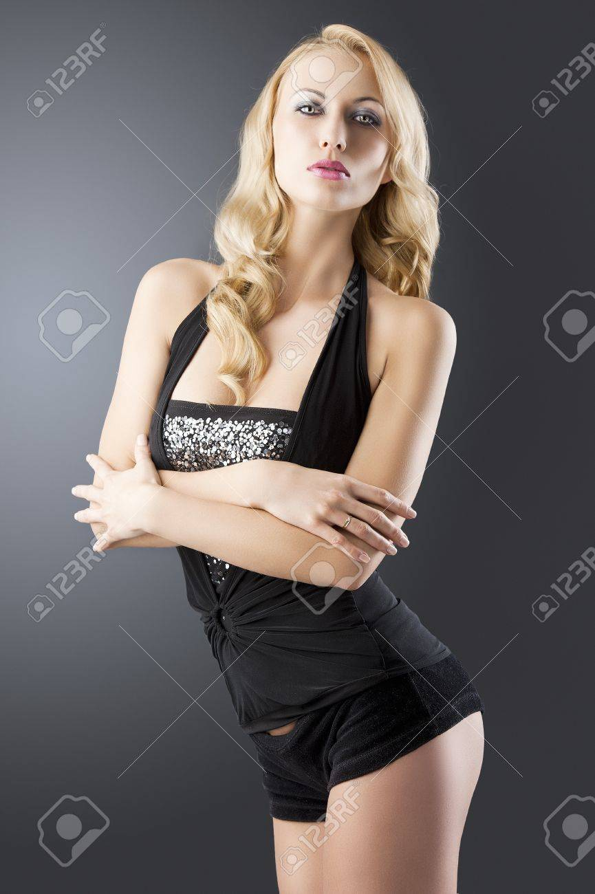 elegant and sexy woman in black with shorts and with a curly hair style over black background, her body is turned of three quaters at right, her arms are crossed and she looks in to the lens Stock Photo - 13529774
