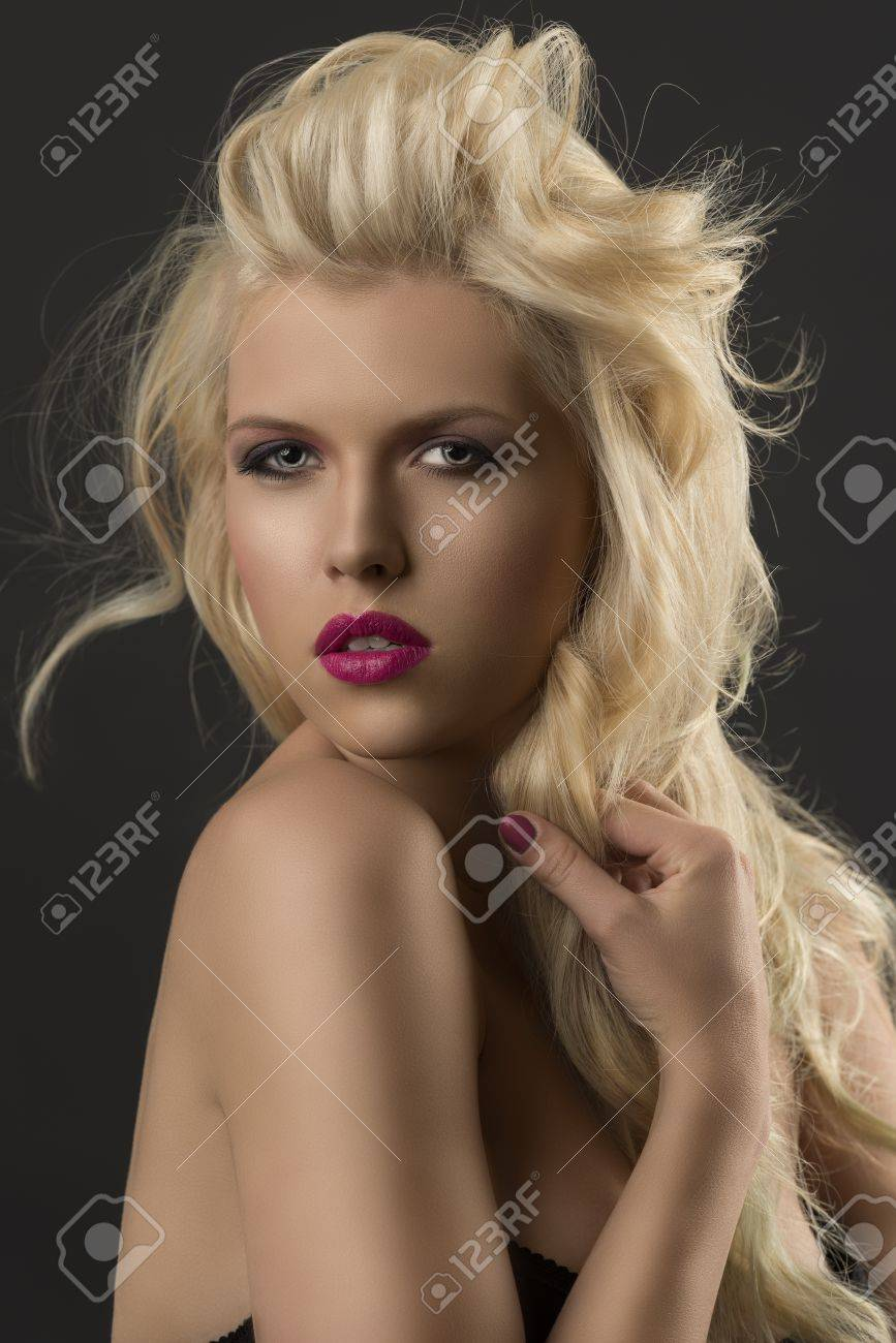 portrait of young sexy girl with blode wavy hairstyle and and flying hair from wind, she looks in to the lens and touches one lock oh hair with right hand Stock Photo - 14705098