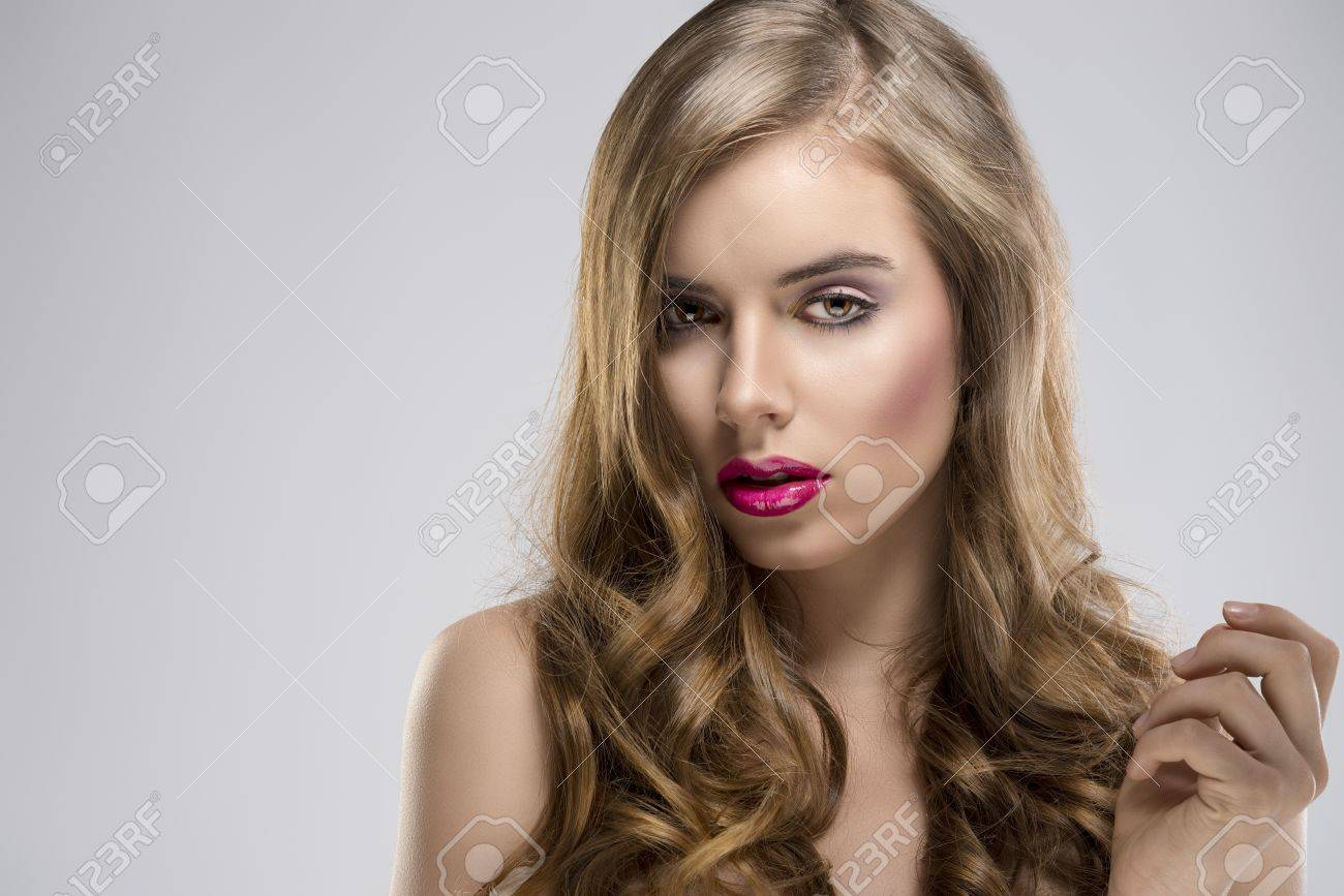 pretty girl with flowing wavy hair and purple make-up, she is turned of three quarters at right and looks in to the lens Stock Photo - 16732302