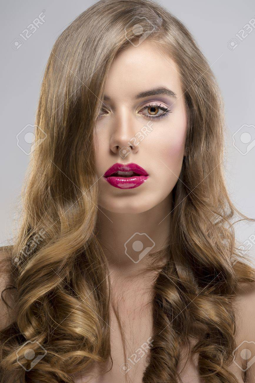pretty girl with flowing wavy hair and purple make-up, she is in fornt of the camera, looks in to the lens Stock Photo - 16732306