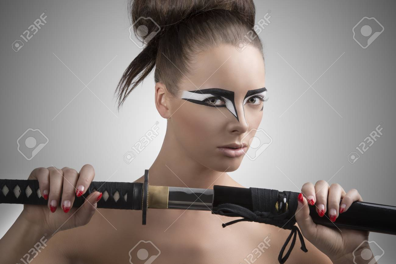 pretty brunette with japan make-up japan sword, her face is turned of three quarters at left and she takes the sword with both hands Stock Photo - 18501451