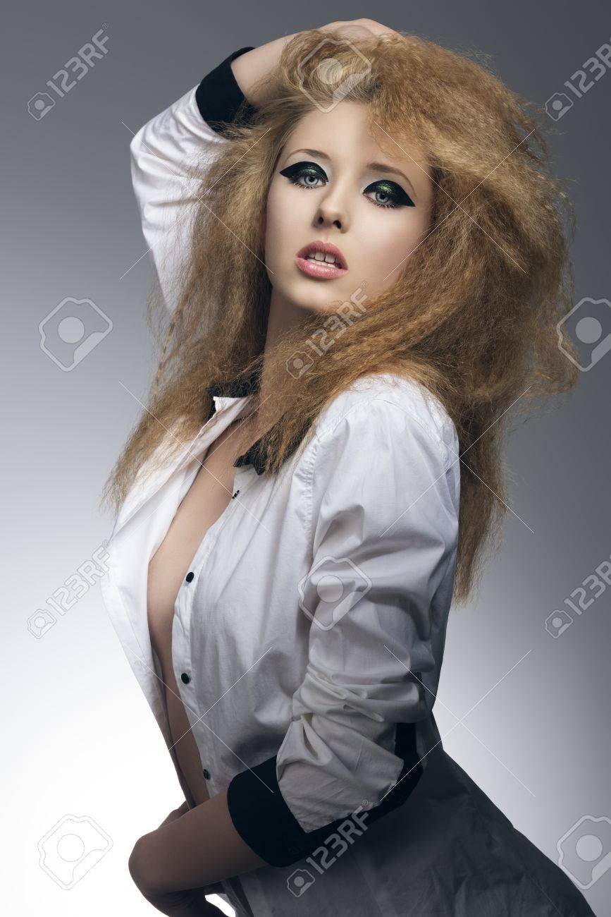 sexy blonde girl in sensual pose on gray background with dark glossy  make-up,