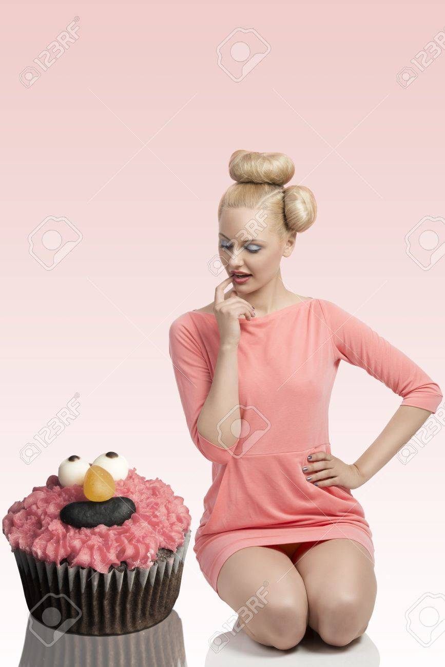 pretty blonde girl with colorful make-up and creative hair-style kneeling on the floor with big cupcake Stock Photo - 20048411
