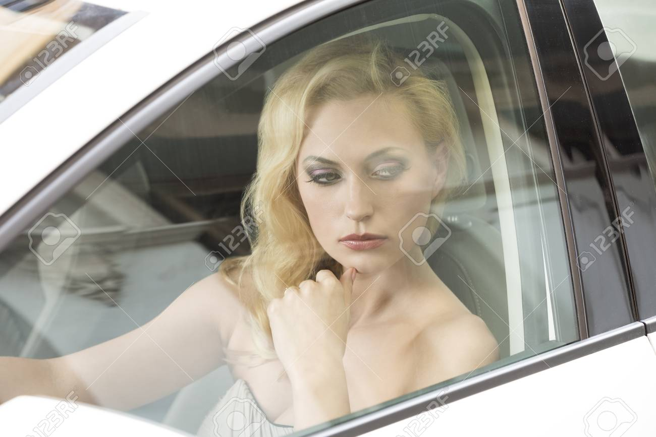 sexy blonde girl with thoughtful expression and elegant style posing in a white car Stock Photo - 26362351