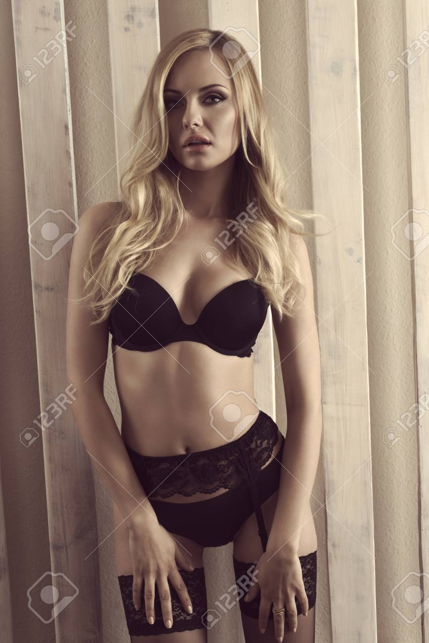 f5dfd0abcf40 Stock Photo - young blonde woman with sexy body posing with black lace  lingerie and looking in camera with sensual eyes