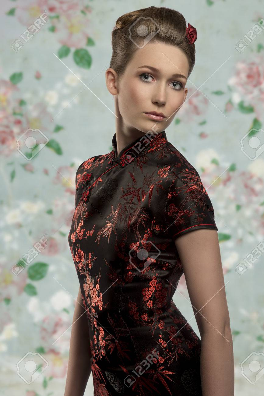 pretty caucasian girl posing with elegant hair-style wearing sexy japanese  dress and looking in