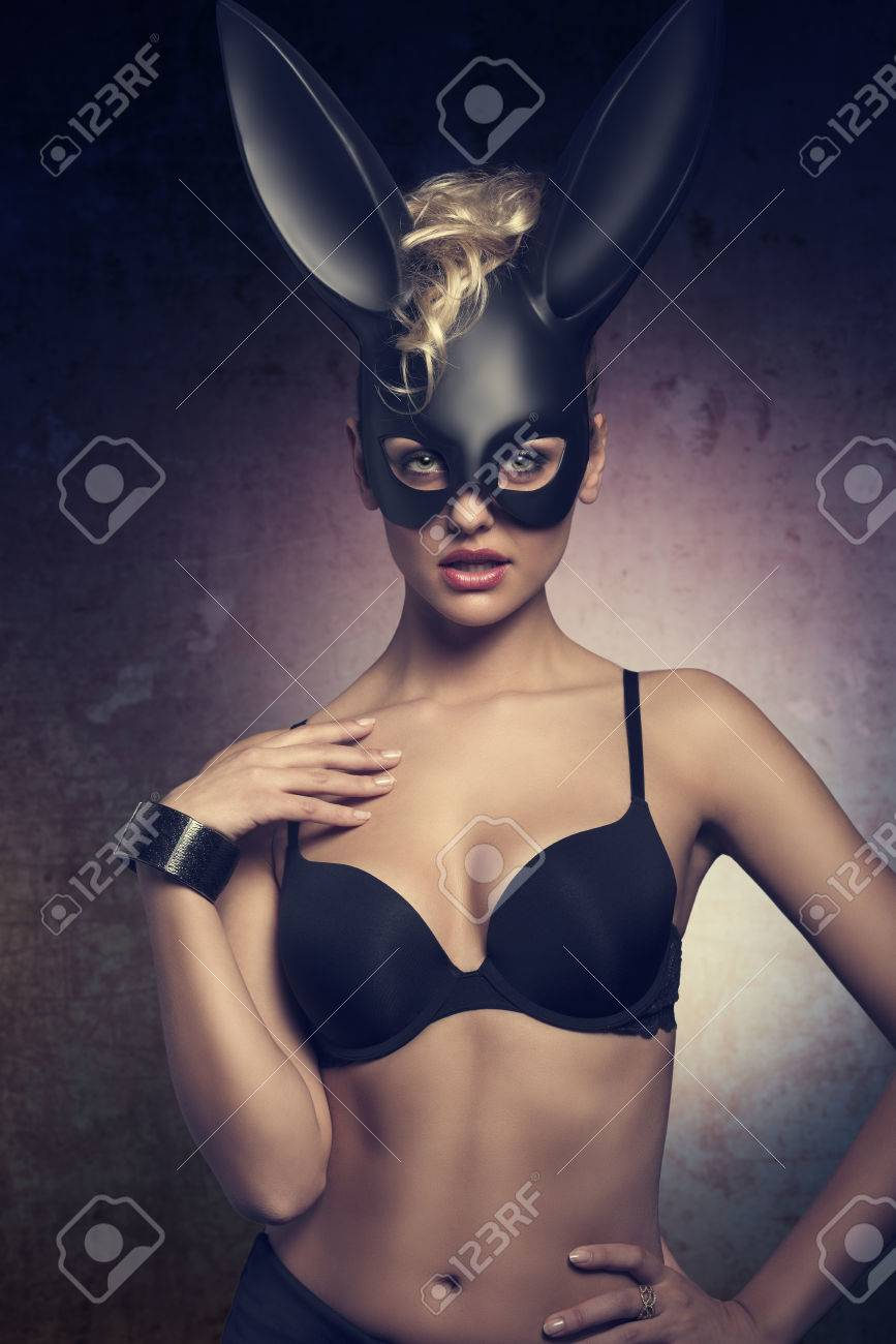 Erotic easter female portrait dark very sexy blonde curly hair style black lingerie wearing bizarre dark bunny mask