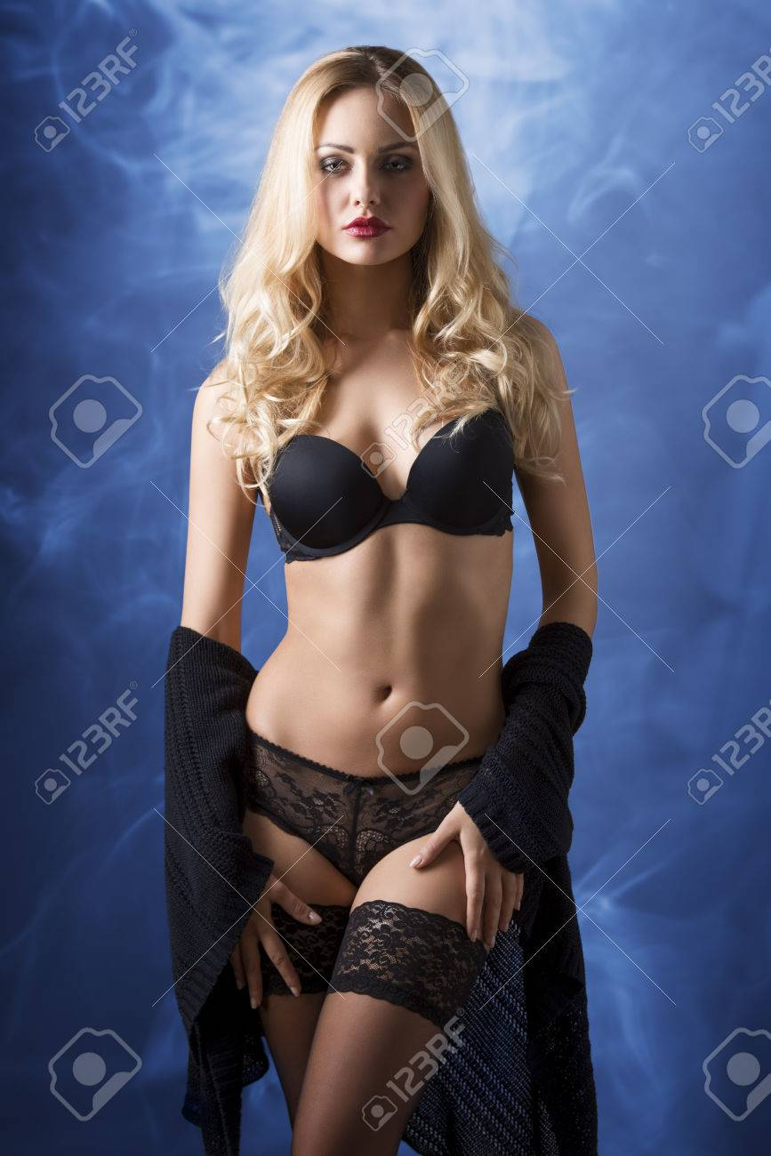 81543cc9fb9c Stock Photo - very sexy blonde woman with long hair and stylish make-up wearing  black lingerie and lace stockings, in sensual pose with fit body