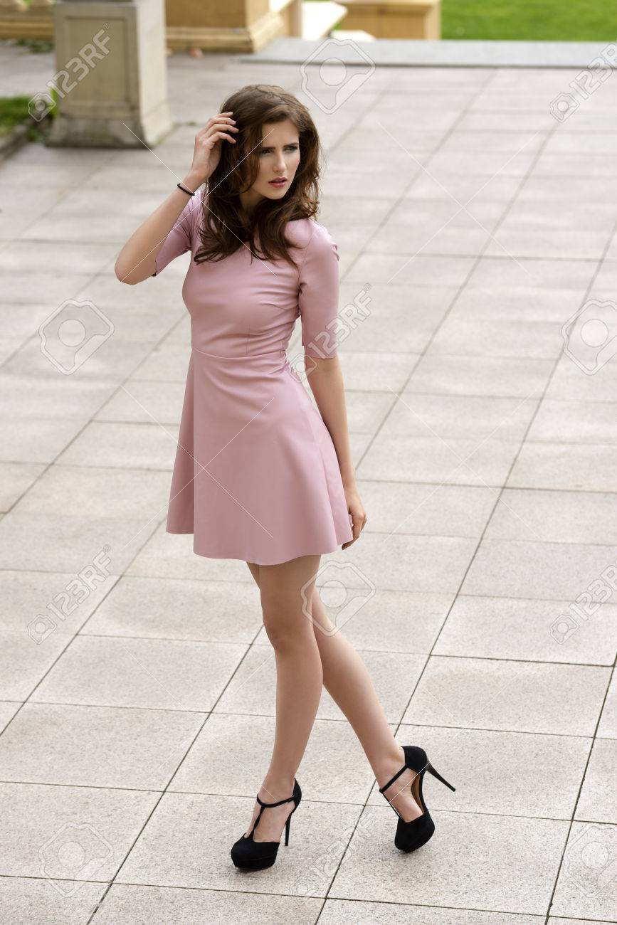 6621a2866e0d outside portrait of elegant brunette female wearing sexy pink dress and  cute black heels. Natural