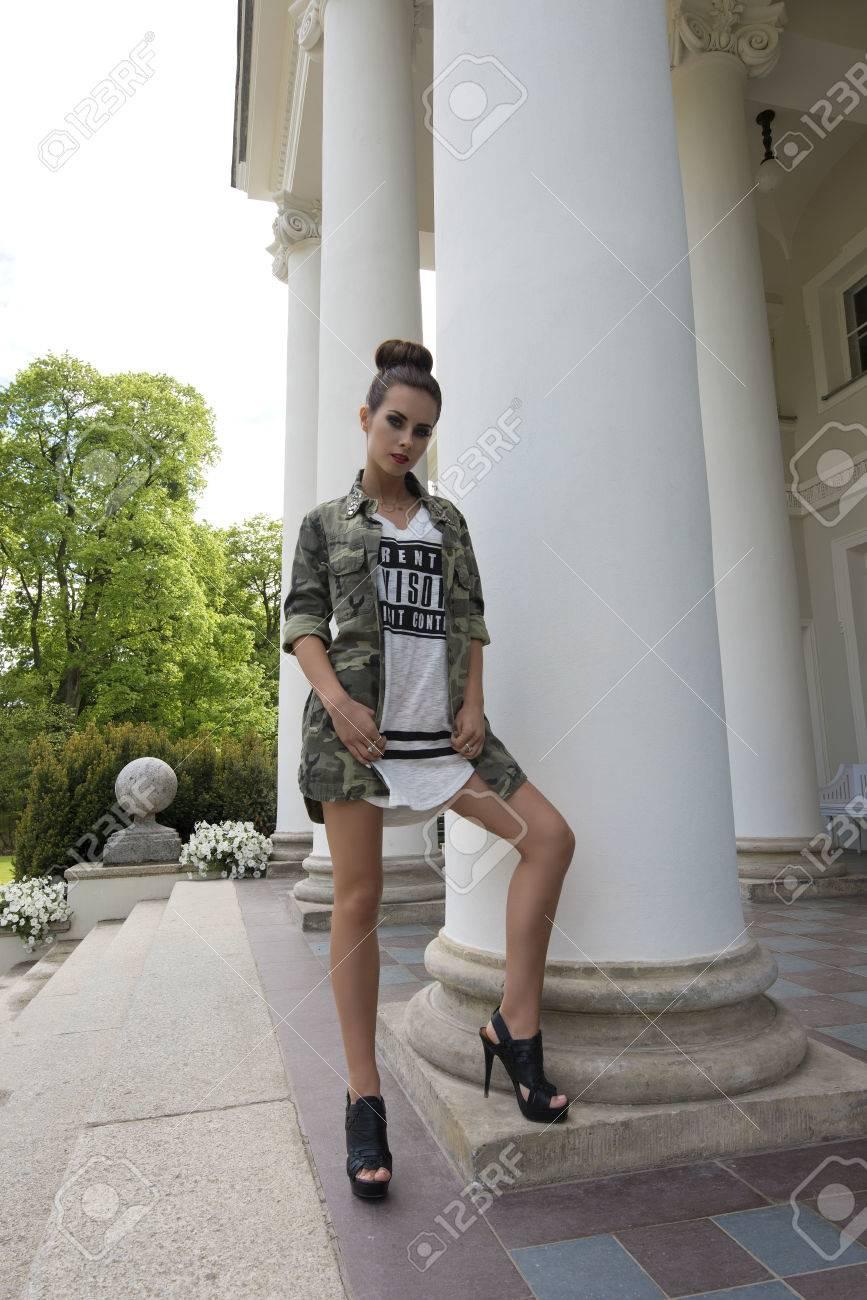 a54820ca744 스톡 콘텐츠 - 짧은 드레스와 발 뒤꿈치 군사 셔츠, 짙은 메이크업 카메라를 찾고 및 오래된 건물의 열 근처 포즈와 귀여운 갈색 머리  여자의 야외 패션 촬영