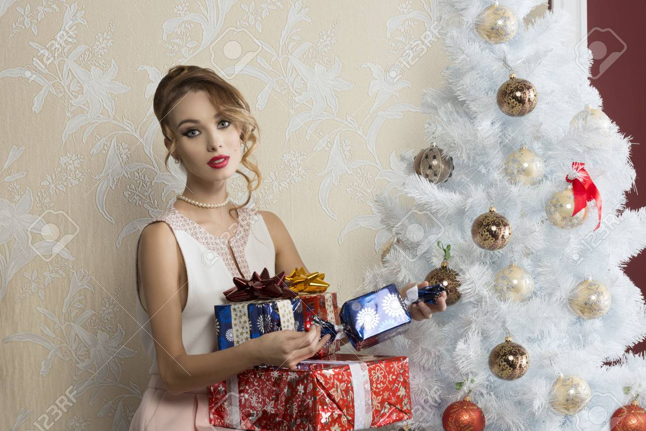 495497a95 christmas portrait of stunning elegant fashion girl with some gift boxes  near decorated xmas tree Stock