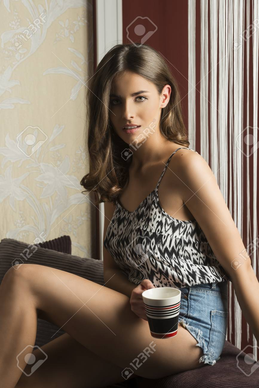 Stock Photo Young And Beautiful Sexy Brunette In Short Looking In Camera And Bringing A Cup Of Tea In A Cold Winter Day Sitting On Her Sofa At Home