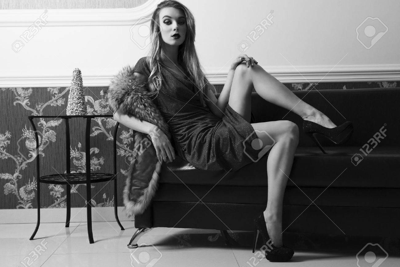 5e55910277bb Splendida donna è seduto in posa sexy sul divano in pelle in ambiente elegante  con abito da sera blu