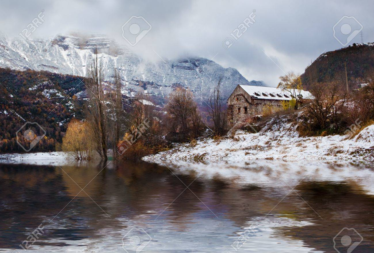 Snowy mountain landscape with house and lake Stock Photo - 9866884