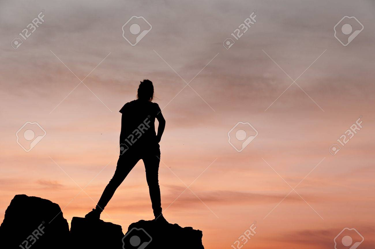 Silhouette of young woman dancing on a few rocks at the sunset - Horizontal Stock Photo - 16747798