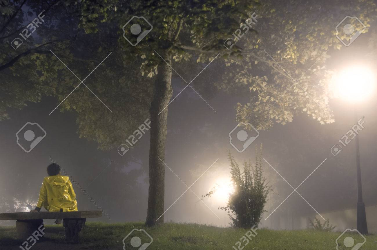 Woman Sitting Alone On A Park Bench In A Mysterious Foggy Night