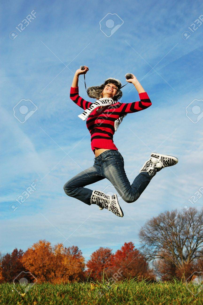 Happy girl jumping of joy on a fall day - 7774212