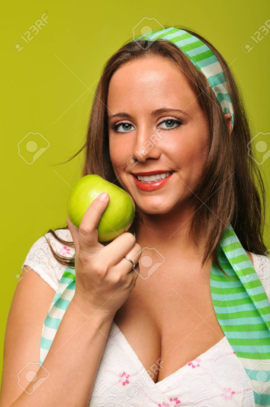 Brunette holding apple and smiling against a green background Stock Photo - 7889335