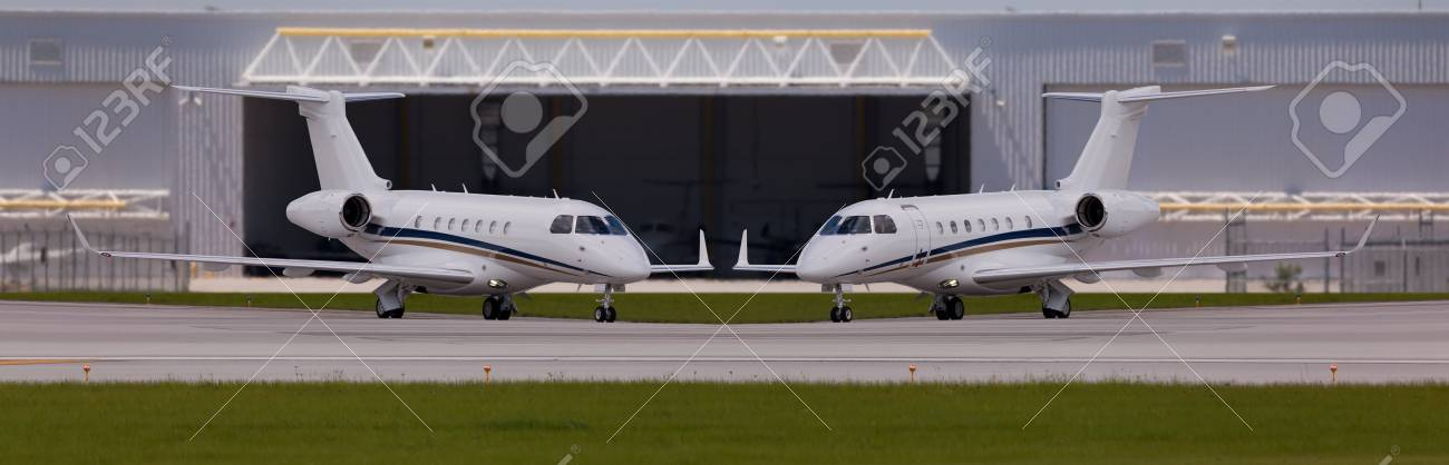 Two private planes in front of a hangar - 50728342