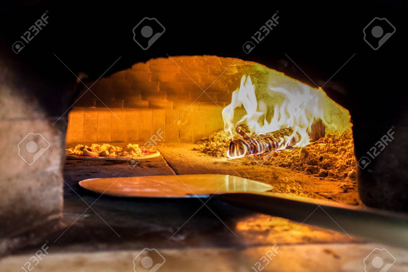 Wood oven of a restaurant with pizza. - 47626405