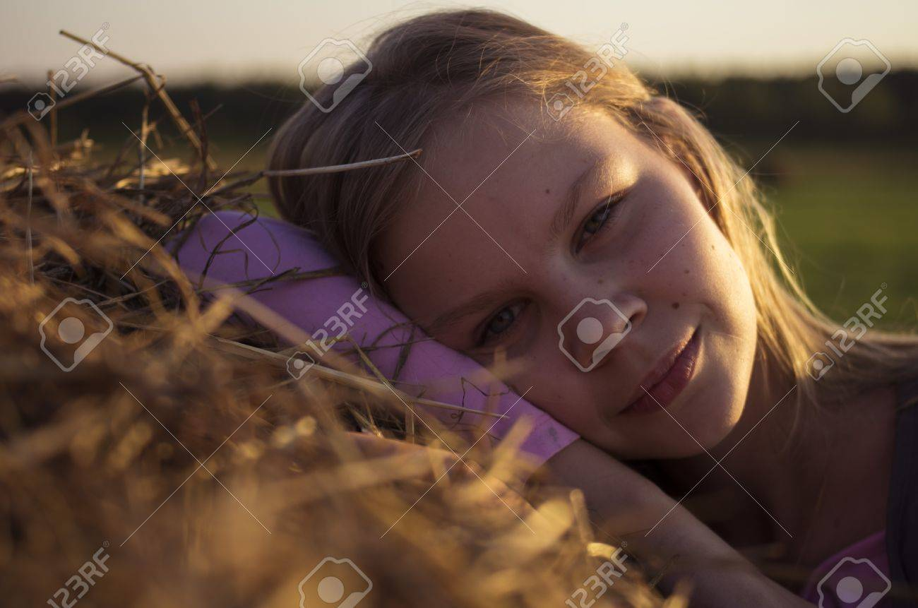 Portrait of teenage girl in the field with corn ears and straw Stock Photo - 14904228