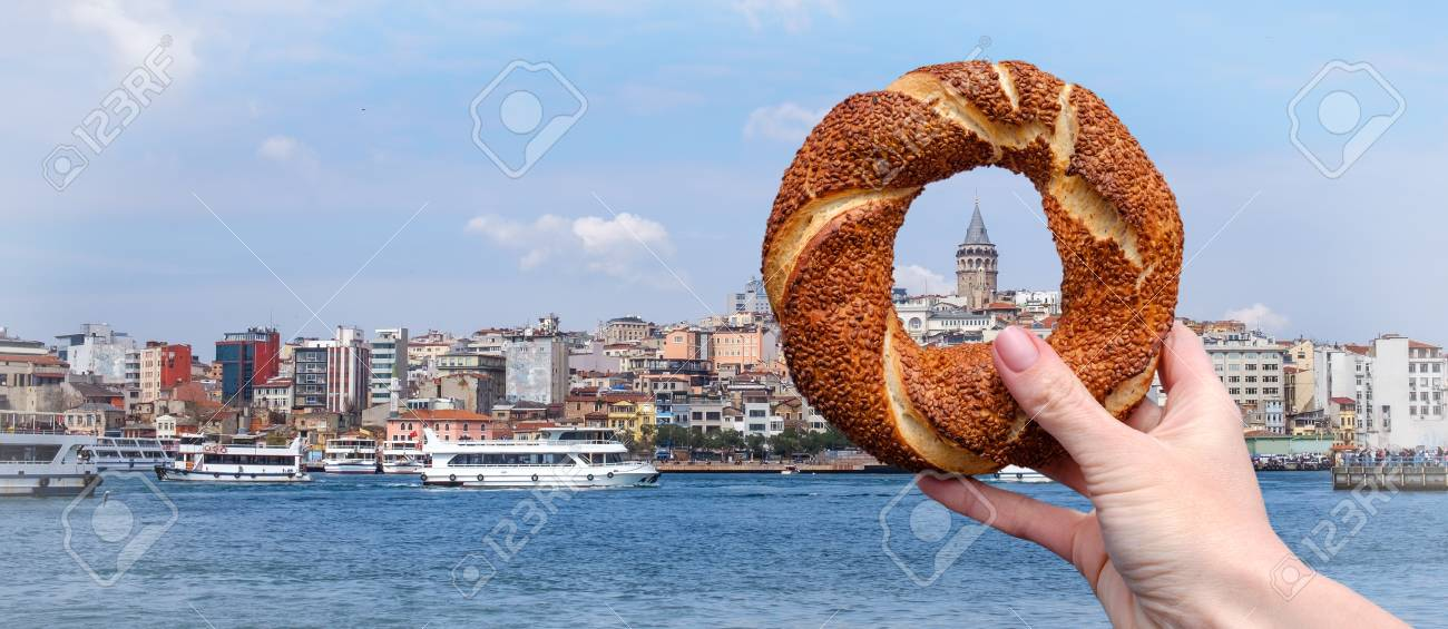 Traditional Turkish bagel simit in a female hand on the background of the panorama of Istanbul and the Galata Tower, horizontal banner - 120535666