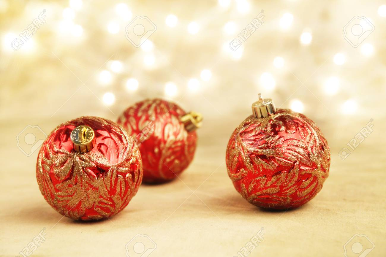 14988108 red and gold christmas ornaments on gold background with white lights