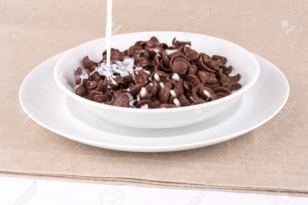 Milk Pouring Into A Dish With Chocolate Cereal Flakes. Stock Photo ...