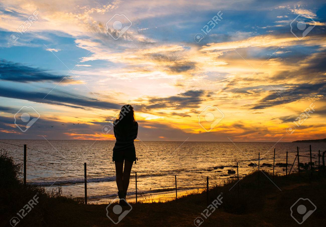 Silhouette of a Pensive Woman Standing at the Beach and Facing at the Peaceful Ocean During Sunset Time. - 44866494