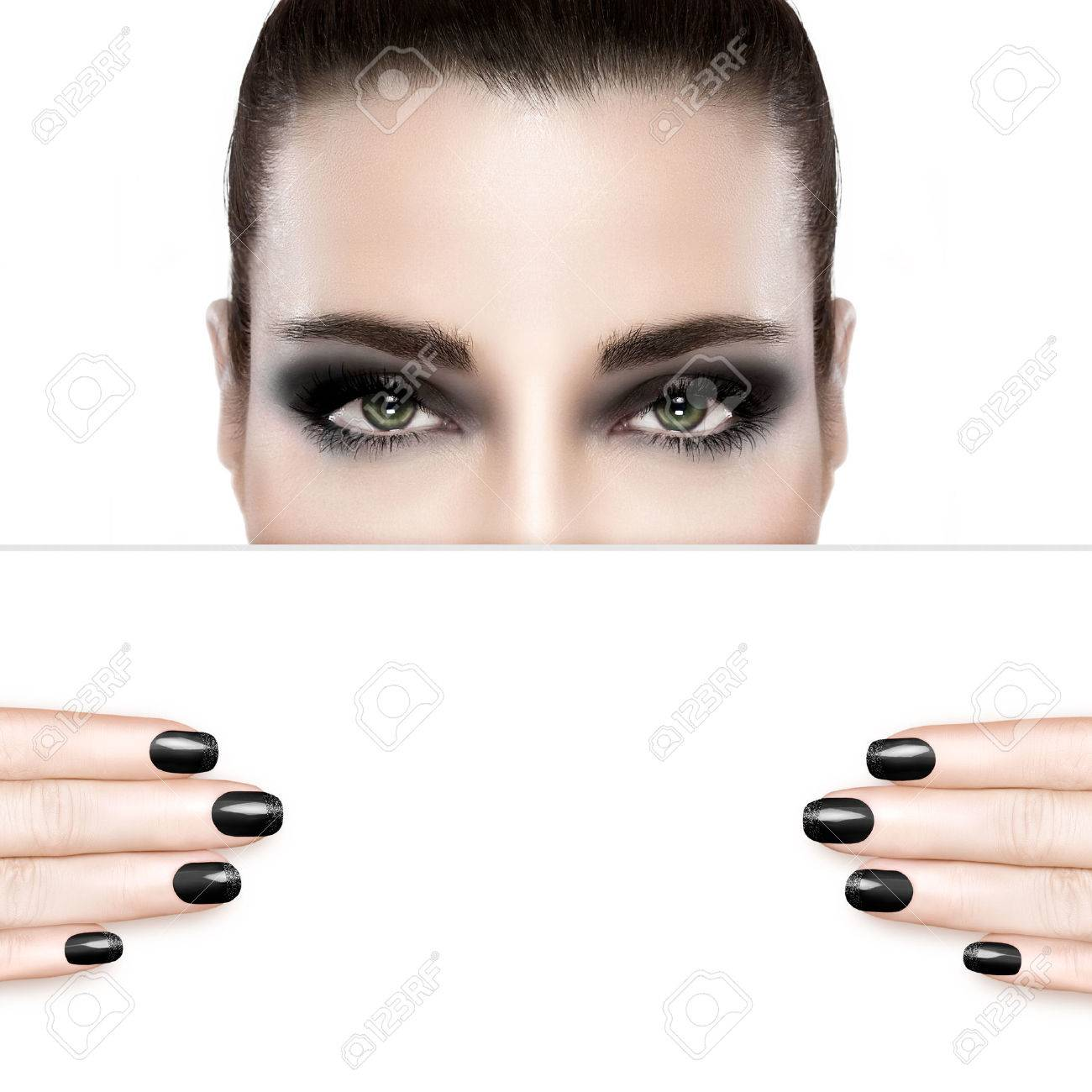 Dark smoky beauty and nail art concept with a woman wearing creative dark eye makeup holding a blank white card template covering her mouth with matching dark manicured nails. Portrait isolated on white with copy space for text. - 46755164