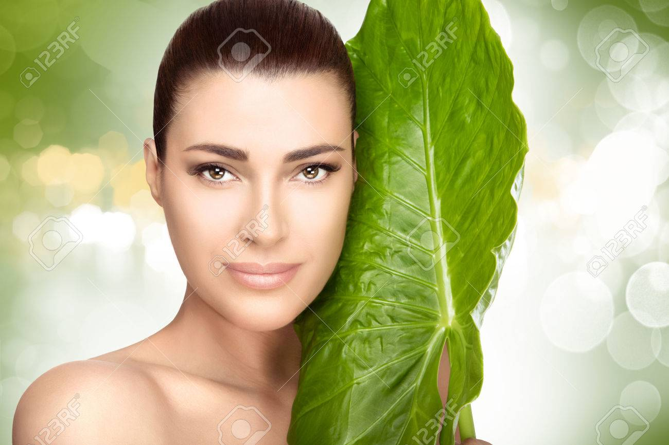 Beauty portrait of an attractive natural young girl with a large fresh green leaf held to her cheek against a soft green bokeh background in a spa and wellness concept - 54110300