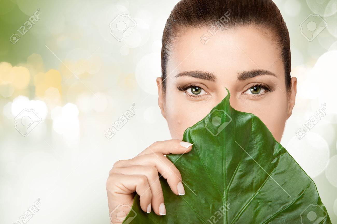 Gorgeous young brunette woman with a fresh leaf from a tropical plant held to her face covering mouth and nose in a spa and beauty concept. Portrait over soft green bokeh background with copy space - 54110296