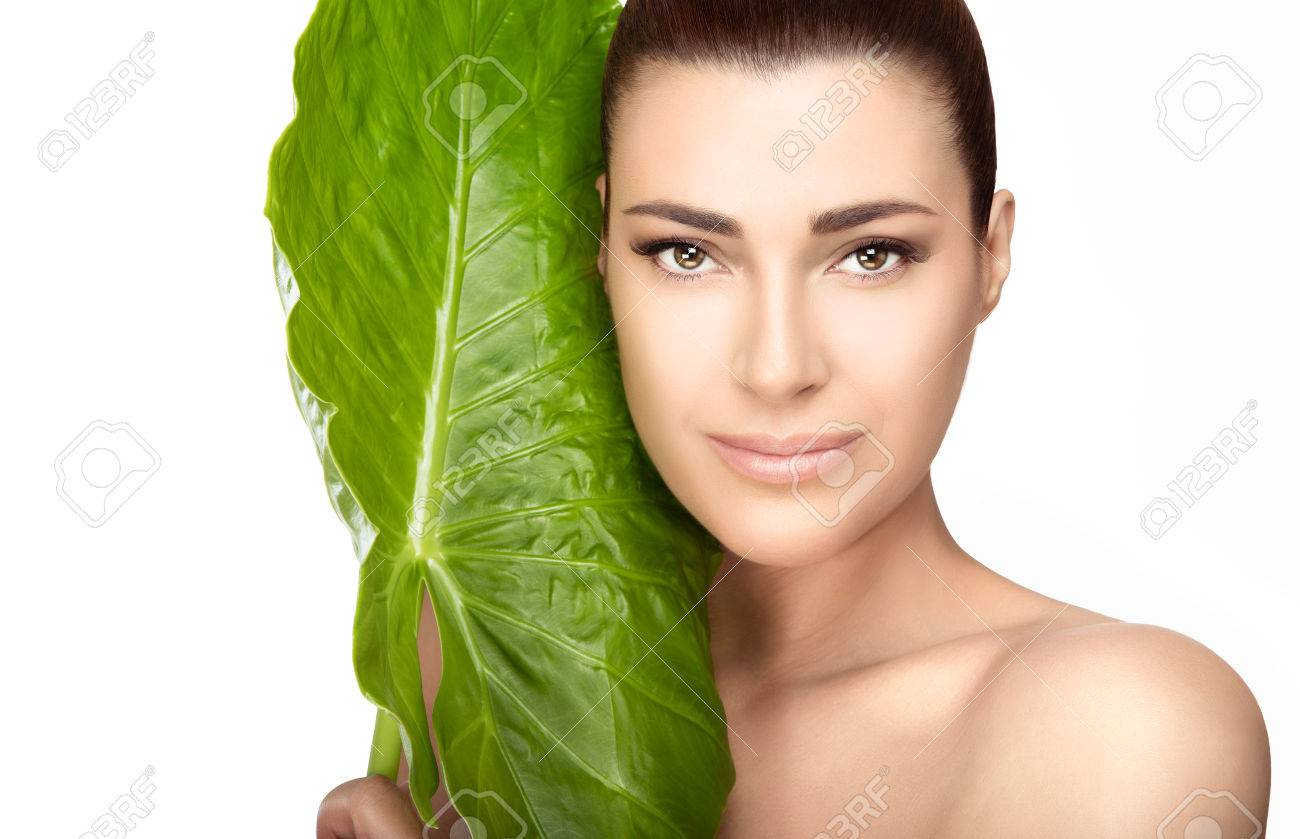 Beauty and skincare portrait. Beautiful spa girl with the large fresh green leaf of a tropical plant against her cheek as she looks at the camera with a gentle smile in a spa and wellness concept - 55314682