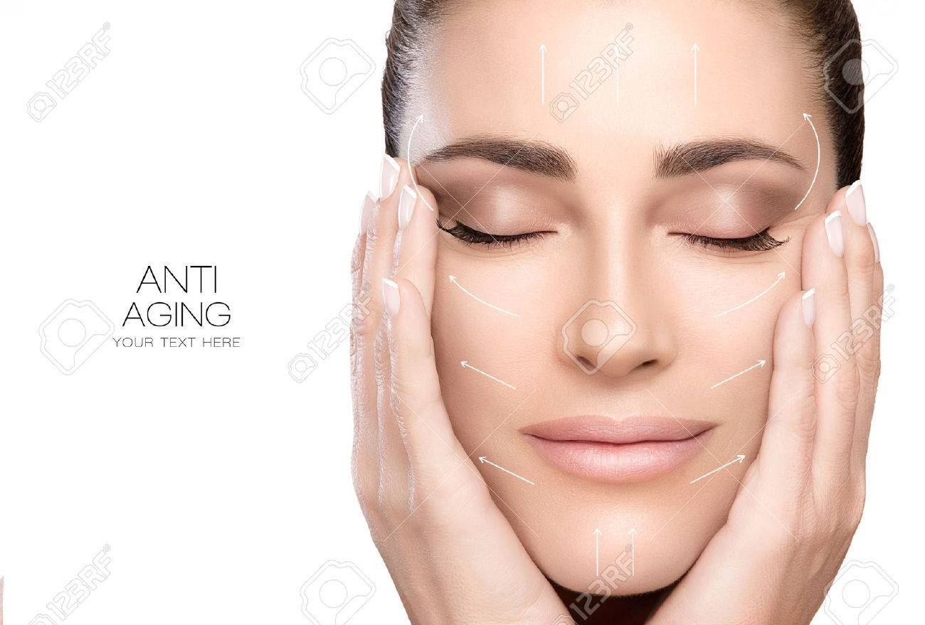 Anti aging treatment and plastic surgery concept. Beautiful young woman with hands on cheeks and eyes closed with a serene expression and white arrows over face. - 58030078