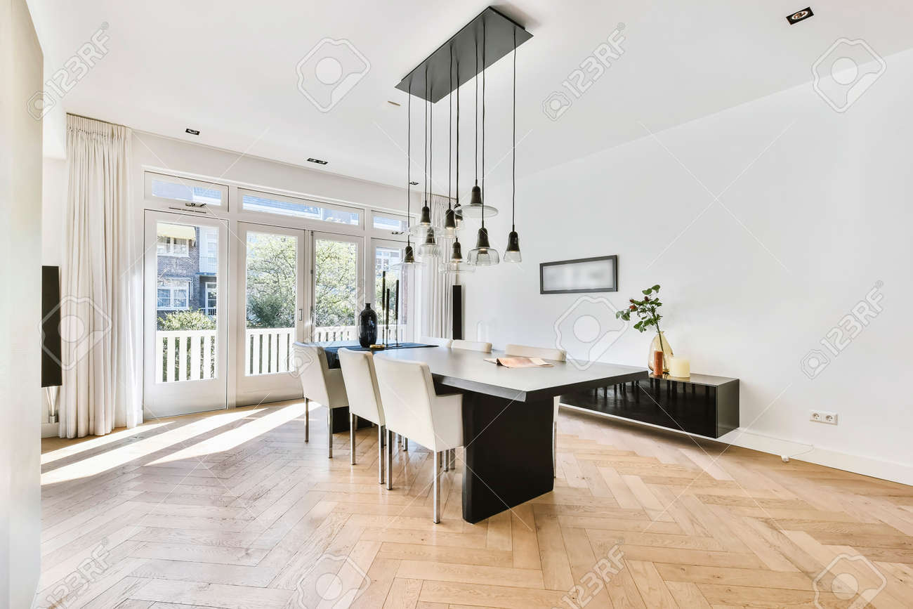 Stylish interior with parquet floor and contemporary minimalist furniture of dining table and chairs under pendant lamps - 169596979