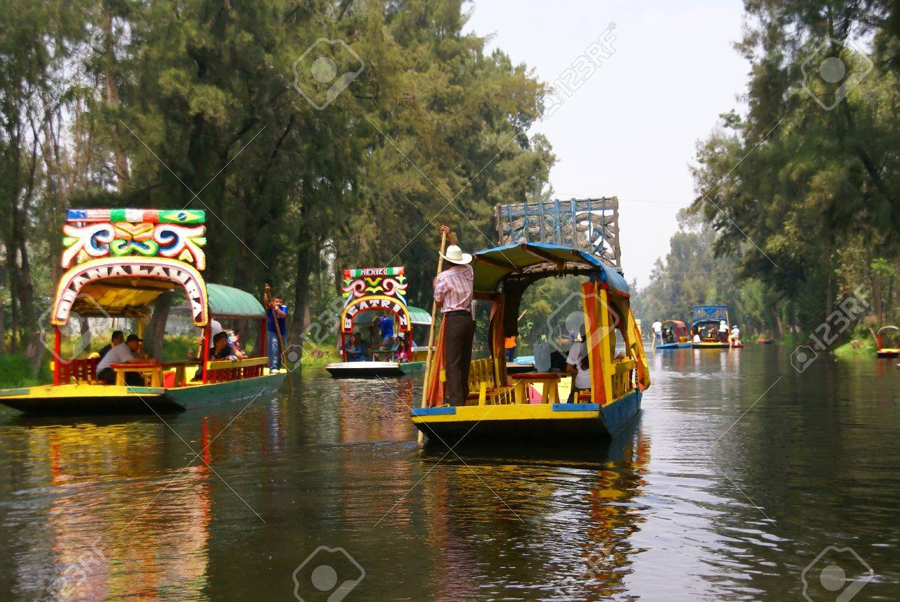 Xochimilco Mexico City 3 SEP 2008 - Boatman poling brightly colored boat, Xochimilco canals, floating gardens, Mexico City - 11458445