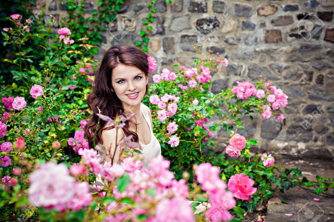 Portrait Of Young Beautiful Woman In The Rose Garden